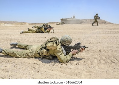 Squad of Israel army combat soldiers firing an assault rifle. Infantry soldiers firing at terror targets. Warrior shooting in prone position during military training in desert landscape.