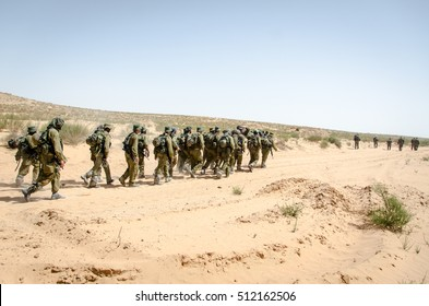 Squad of Israeli elite unit combat soldiers carrying a wounded friend on a stretcher through a sandy desert after a fierce battle against terrorists. Infantry battalion  soldiers in training.