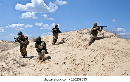 Squad of soldiers run through the desert through the military operation