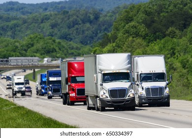 A squadron of eighteen-wheelers lead the way down an interstate highway in eastern Tennessee.  Heat waves rising from the pavement give a shimmering effect to vehicles and forest in the background.