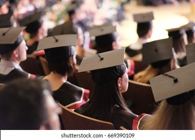 Square academic caps of graduates sitting in the university hall at the presentation of diplomas.