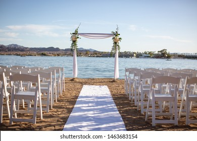 Square arch with flowers and fabric draping over it on beach in front of lake with rows of white chairs, looking down the aisle.