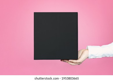 A square black box with an copy empty space for text and design in the hand of a young woman in a white shirt on a pink background. Board, blank, template, mockup, layout for a slogan or inscription.