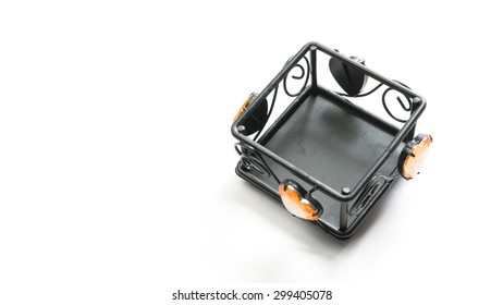 Square black colour metal candle holder with love shape accessories. Isolated on white background. Slightly de-focused and close-up shot. Copy space.