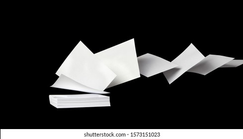 Square blank white papers flying away from a stack in the wind, on black