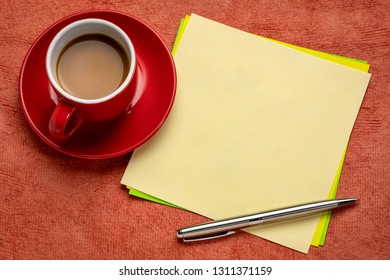 square blank yellow note with a cup of espresso coffee and pen against textured paper