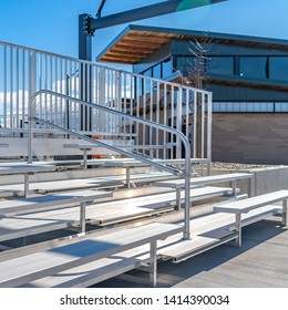 Square Bleachers with railings against a building and cloudy blue sky