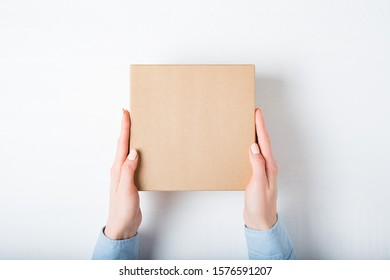 Square cardboard box in female hands. Top view, white background