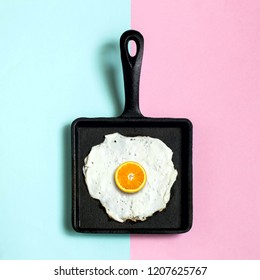 Square cast-iron frying pan with fried eggs, half of orange instead of yolk. Artificial objects that mimic natural forms. Creative idea, imagination and fantasy. Original minimal concept