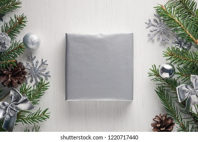 Square Christmas gift wrapped in clean silver paper with copy space on white background surrounded by spruce twigs, pine cones and silver decorations. Flat lay style
