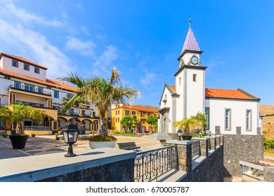 Square with church building and colourful buildings on coast of Madeira island, Portugal