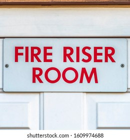 Square Close up of the Fire Riser Room with white wooden door of a brick building