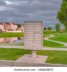 Square Cluster mailbox against pond and houses under sky with thick gray clouds