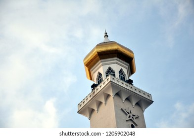 square column of a minaret capped by golden dome with pointed spires