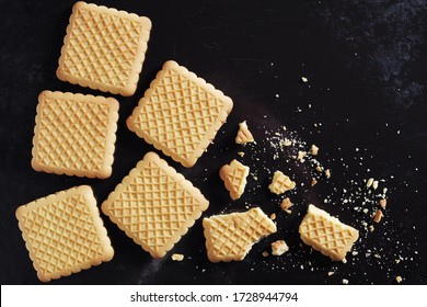 Square cookies whole and broken on old black metal background, top view