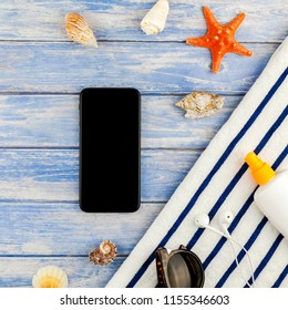 Square Creative flat lay concept of summer travel vacations. Top view of beach towel smartphone seashells starfish on pastel blue wooden planks background with copy space mockup template for text