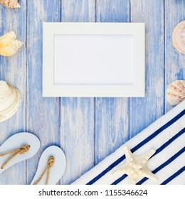 Square Creative flat lay concept summer travel vacations. Top view of towel flip flops seashells and starfish on pastel blue wooden planks background with copy space rustic style frame template text