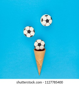 Square Creative flat lay top view of ice cream waffle cones with soccer balls macarons on bright bold blue background with copy space in minimal style, concept of football games for children birthday