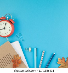 Square Creative flat lay top view back to school concept with alarm clock color school and office supplies on bright turquoise paper table frame background with copy space, template for text or design