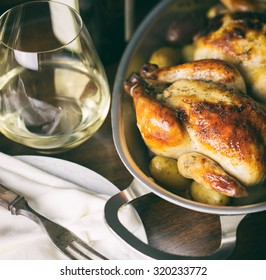 Square crop of baked Cornish hens and a glass of white wine.  Analog filter applied.
