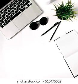 Square crop. Stylish minimalistic workplace with laptop keyboard, notebook, sunglasses and office plant in flat lay style. White background. Top view.