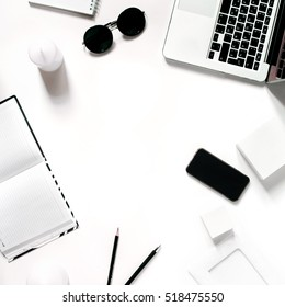 Square crop. Stylish minimalistic workplace with laptop keyboard, smartphone, notebook, sunglasses in flat lay style. White background. Top view.