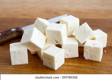 Square cubes of feta cheese isolated on wood board with knife.