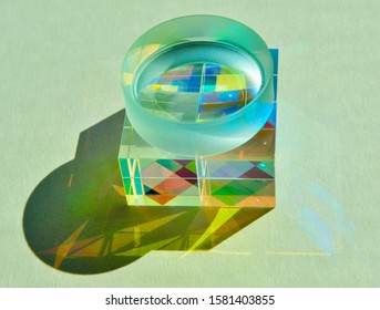 Square dichroic glass cube prisms placed underneath concave lens dispersing beam of sunlight into vivid spectrum colours. Refraction of light creates optical effect and reflection inside
