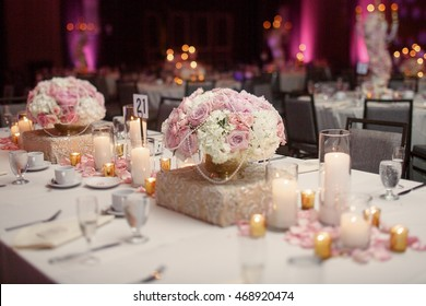 Square dinner table served with white crockery and decorated with white and golden candles
