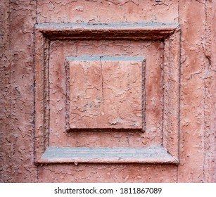 Square door ornament on an old door with peeling Burgundy paint. Square rhombus shape frame architecture background. Geometric carpentry wall. The predominance of maroon color