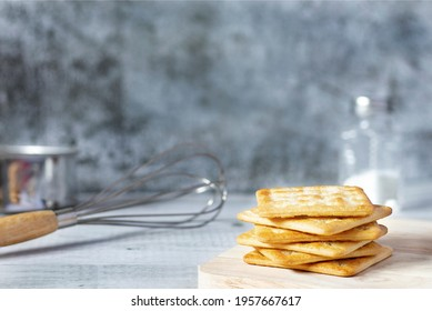 square dry crackers on a wooden table. concrete texture background. Snack dry Biscuits healthy whole wheat tasty crispy crackers cookies for children and adults have Free space for text, front view