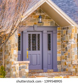 Square Facade of a home with a beautiful stone wall and gray front door