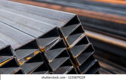 Square flat-rolled pipe metal profile in packs at the warehouse of metal products. Weathered metals profiles for construction. Metal corrosion.