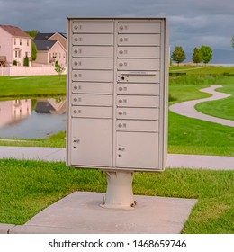 Square frame Cluster mailbox against pond and houses under sky with thick gray clouds