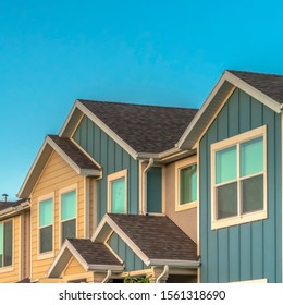 Square frame Exterior of upper storey of townhomes with blue sky background on a sunny day