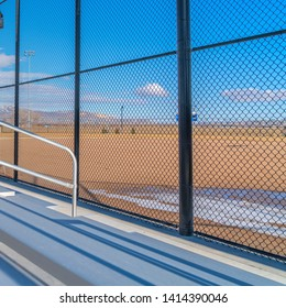 Square frame Sunlit bleachers overlooking a vast sports field on the other side of the fence
