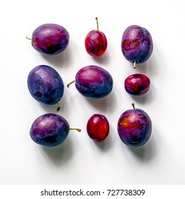 Square of fresh plums.  Food Photo. Creative scheme of whole plums on white background. View from above.