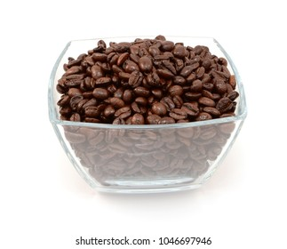 Square glass bowl full of roasted coffee beans, on a white background