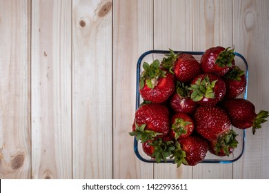 square glass bowl with strawberries on a light wooden table. Big strawberries.