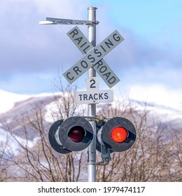 Square Grade crossing signal with red light gate and crossbuck at railroad crossing. Traffic signal against snowy mountain, cloudy blue sky, and trees with leafless branches.