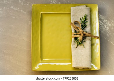 Square green plate with natural coloured napkin and space for copy.