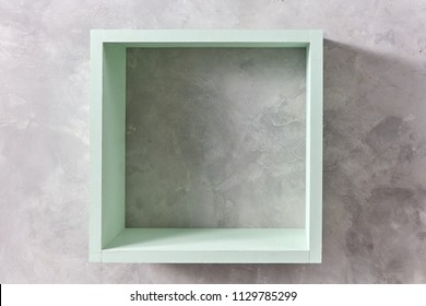 square green wooden wall isolated on gray concrete wall with copy space. Product display template