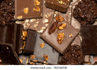 square hand made pieces of chocolate ornated with almonds, nuts and chestnuts.