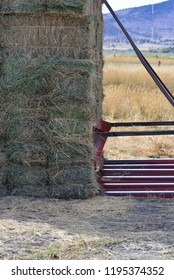 Square hay bales being stacked.