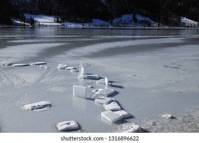 Square ice blocks on a frozen water surface. Sunny winter day on a lake in the Bavarian Alps. Randomly left ice quadrangles in the foreground, lakeside with snow in the background. No persons.