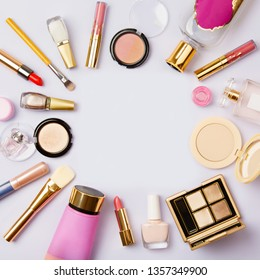 Square image of cosmetics for social media with empty place for text. Woman make up cosmetics on purple. Copy space. Gold and purple decorative cosmetic: highlighter, concealer, rouge, eye shadows etc