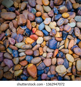 Square image of different kind of colorful pebbles stones wall texture. Abstract nature background of beautiful sand stone floor in garden or park. Sea  cobblestone or river rock stones wallpaper.