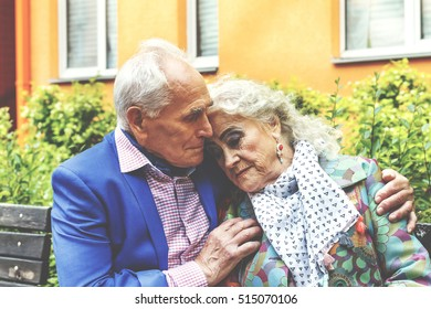 square image. Elderly man tenderly embracing his elderly wife on a bench near a residential building in a modern city.