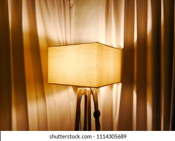 Square lamp made of linen and stand made of wood. It is located in the corner of the room with beige curtains in the back. Selective focus and copy space.