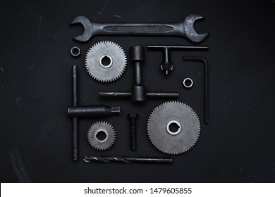 Square layout of different tools on dark background. Wrench tools, gear wheels, ring spanners, monkey wrenches, cogwheel, screws and bolts. Father's Day concept. Do it yourself. Flat lay